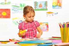 Learning to glue. Clever 4 years old girl holding glue by the table in art lesson in kindergarten Royalty Free Stock Photos