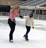 Learning To Ice skate. An instructor teaching a young girl how to ice skate in the rink at Rockefeller Center, Manhattan, NY Stock Image