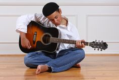 Learning to Play. A teenage boy practicing his guitar royalty free stock photos