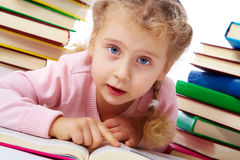Learning to read. Portrait of a little girl among books Stock Image