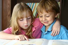 Learning to read. Young girl helping a young boy to read a book royalty free stock image