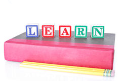 Learning To Read. Learn Written With Alphabet Blocks On Hardcover Book With Pencils Royalty Free Stock Image