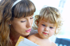 Learning to read. High key portrait  of young mother reading a book for her baby . focused on baby's face Royalty Free Stock Images
