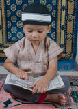 Learning to read Quran. A Muslim boy learn how to read the Holly Quran stock images