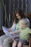 Learning to Read. A toddler points to something in a book as he sits with his mother on a wooden swing Royalty Free Stock Photography