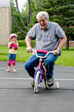 Learning to ride a bike with training wheels Royalty Free Stock Photography