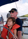 Learning to Sail. Young girl at the helm of a sailboat with her grandfather assisting Stock Photo