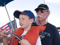Learning to Sail With Grandpa. Young boy at the helm of a sailboat with Grandpa watching closely Royalty Free Stock Images