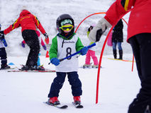 Learning to ski. 4 years old boy is learning the snowplough turn in a ski school by passing a slalom Stock Photography