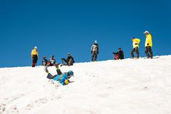 Learning to slip properly on a slope or glacier with an ice ax Royalty Free Stock Photos