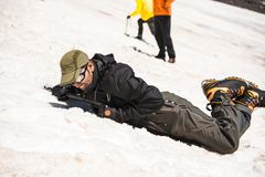 Learning to slip properly on a slope or glacier with an ice ax Royalty Free Stock Images