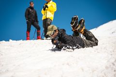 Learning to slip properly on a slope or glacier with an ice ax Stock Photography