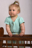 Learning to stand on her own. Baby standing next to cradle Stock Photography