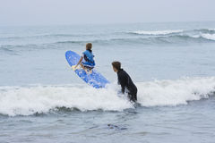 Learning to Surf. A father teaches his son how to surf on the California coastline. The son is being launched on his surf board by a wave Royalty Free Stock Photo