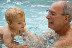 Learning to Swim. A man with silver hair and glasses holding a one year old baby boy with blonde hair and blue eyes in a swimming pool Royalty Free Stock Photography