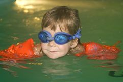 Learning to swim. Two and a half year old girl swimming alone in the pool with arm bands Royalty Free Stock Image