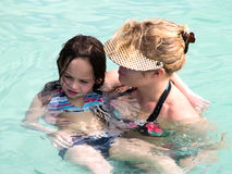 Learning to Swim. A girl being held by her mother while learning to swim in a pool Royalty Free Stock Images
