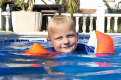 Learning to swim. Young boy wearing inflatible floating wings learning to swim in an outdoor pool royalty free stock photos