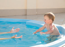 Learning to swim. Little boy learning to swim in the pool with his mother Stock Photo