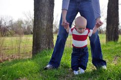Learning to walk. Mother helping her son learn to walk Stock Photography