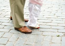 Learning to walk. Father teaches baby to walk outside Stock Photography