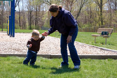 Learning to Walk. Twenty five year old woman helping a one year old boy learn how to walk.  They are near a playground Royalty Free Stock Photo
