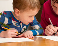 Learning to write. Young four year old boy learning to write with his mother at the table royalty free stock image