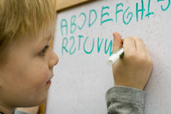 Learning to write. Little boy learning to write alphabet on white board royalty free stock photos
