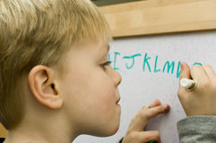 Learning to write. 4 years old boy learning to write alphabet on white board stock photo