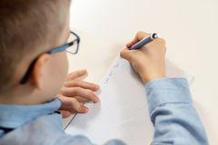 Learning to write. The boy sits at the desk and learns to write with a pen in a notebook. Boy sits at a desk with a pen in his hand and writes in a notebook stock photos