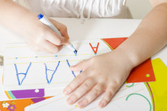 Learning to write. Little child hands writing letter A. Little girl writing alphabet in a copy book at a desk. Learn Study Education School Knowledge Concept Stock Photos