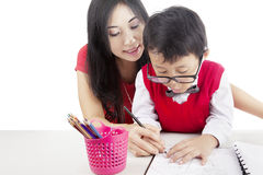 Learning to write with mother. Portrait of elementary school student learn to write with his mother Stock Photo