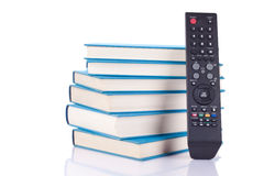 Learning or watching  tv - what is your choise. Group of blue books and remote control - on white Stock Photography
