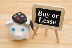 Learning whether to buy or lease car. A piggy bank on a desk with chalkboard and car keys with text Buy or Lease stock images