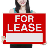 For Lease. A young woman holding a signboard indicating For Lease Royalty Free Stock Image