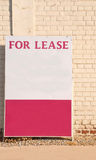 For Lease. Sign against a neutral brick wall Royalty Free Stock Photo