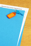 Lease Agreement. Residential Lease Agreement, in a blue file, with key and key fob on top Royalty Free Stock Image