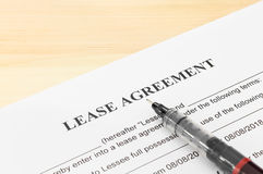 Lease Agreement Contract Document and Pen at Bottom Right Corner. Lease agreement contract sheet and brown pen at bottom right corner on wood table background Stock Photo