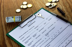 Lease agreement moneyand key on wood table Royalty Free Stock Image