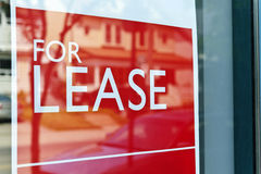 For lease sign. On red in window reflecting street scene Royalty Free Stock Photo