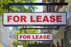 For Lease signs on display outside buildings. Two For Lease signs on display outside buildings during daytime stock photo