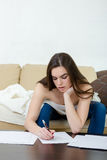 Leasure and home concept - calm teenage girl woman writes with p Royalty Free Stock Photo