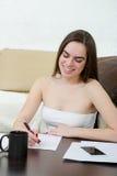 Leasure och hem- begrepp - den lugna kvinnan för den tonårs- flickan skriver med p arkivfoton