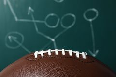 Leather American football on chalkboard. With scheme of game, closeup stock photo