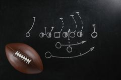 Leather American football on chalkboard. With scheme of game, top view stock photography