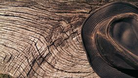Leather Aussie cowboy hat on wood. Wood log background with traditional leather cowboy hat worn in Australia stock images