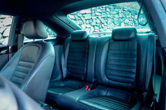 Leather back passenger seats inside coupe sport car. Backside leather passenger seats, coupe sport car, blue tinted windows, inside view from driver side, head Stock Images