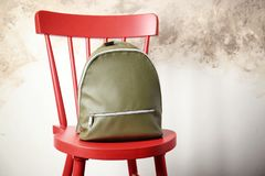 Leather backpack on chair. Against light background Royalty Free Stock Photo