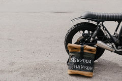 Leather backpack near the motorcycle. Half black motorcycle in the garage. Motorcycle kaferacers. Stock Image