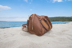 Leather bag on the beach. Leather bag and shoes on the beach Stock Photos